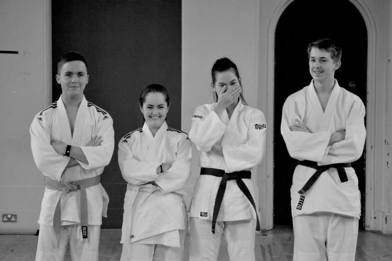 Black and white shot of four judo players, one player has begun to laugh