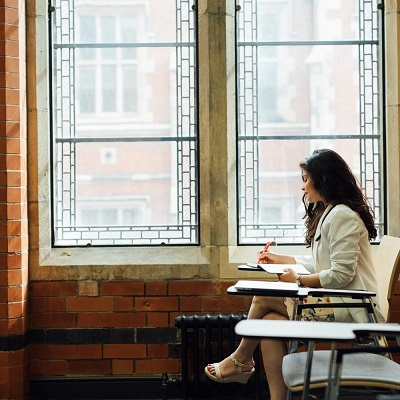 Student sits by a large window, alone, in the graduate centre
