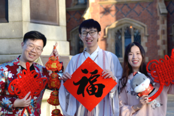 Three students hold up symbols of good luck for the Chinese New Year in traditional dress