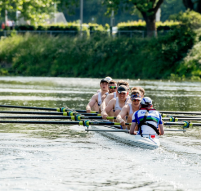 Students rowing down a river in the sun