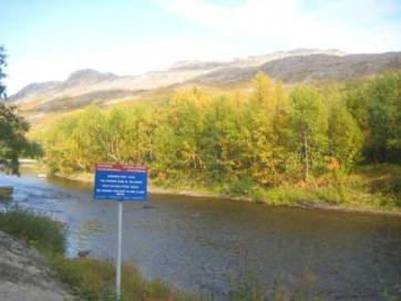 Border between Norway and Russia. The sign reads 'The border runs in the river'. Photo Jaume Castan Pinos (2008).