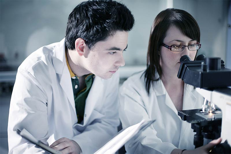 female student examines slides on a microscope whilst a male student takes notes