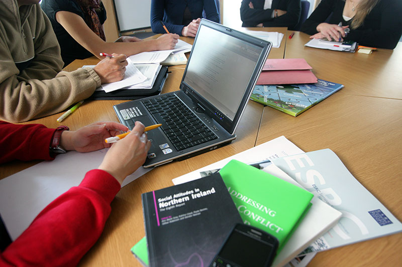 researchers round a table with close ups of research publications in education