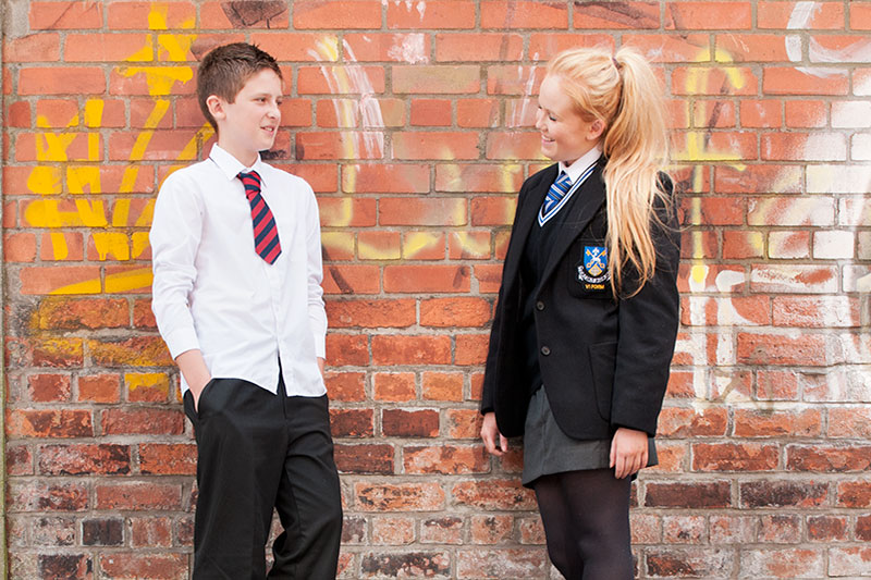 two post-primary pupils from different schools wearing different school uniforms standing against a brick wall covered in graffitti