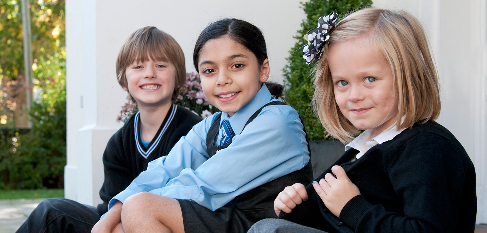 photograph of three primary school children in different school uniforms