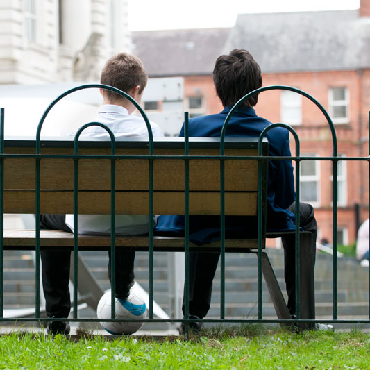 image of two boys wearing differenct school uniforms sitting on a bench