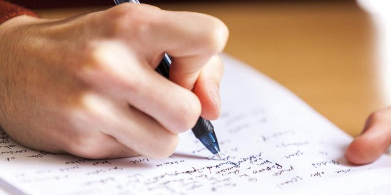 close up of a hand holding a pen and writing notes on a page