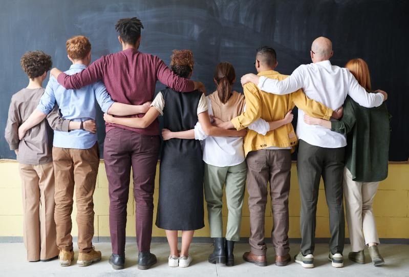 People folding arms with each other face a chalkboard