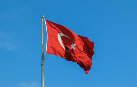 The Turkish national flag is waving with a blue sky background