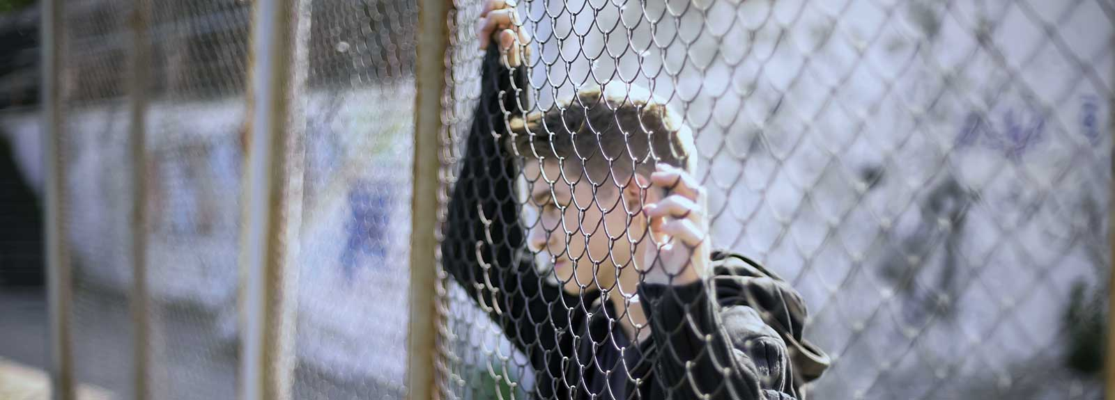 PHOTO: young male behind fence
