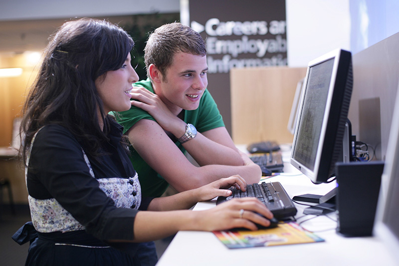 male and female student working on a computer together