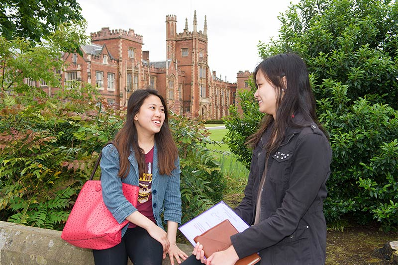 two female students chatting with lanyon building in the background
