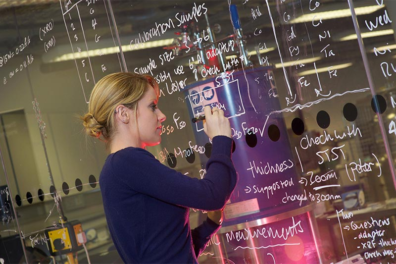 female student writing calculations on a perspex board with white marker