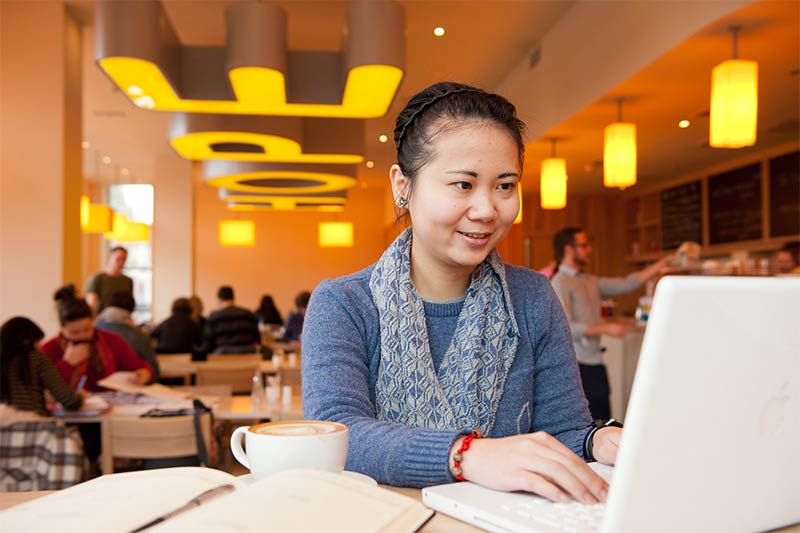 female international student using laptop in Hope coffee shop