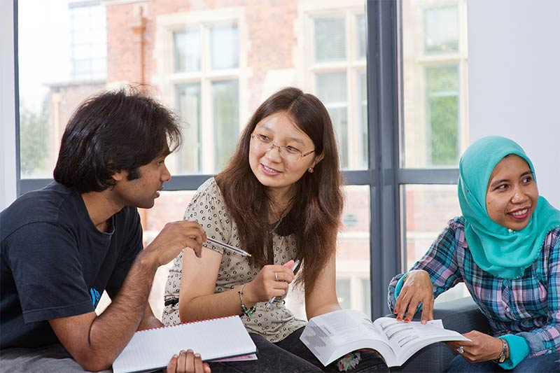 three international students discussing notes together