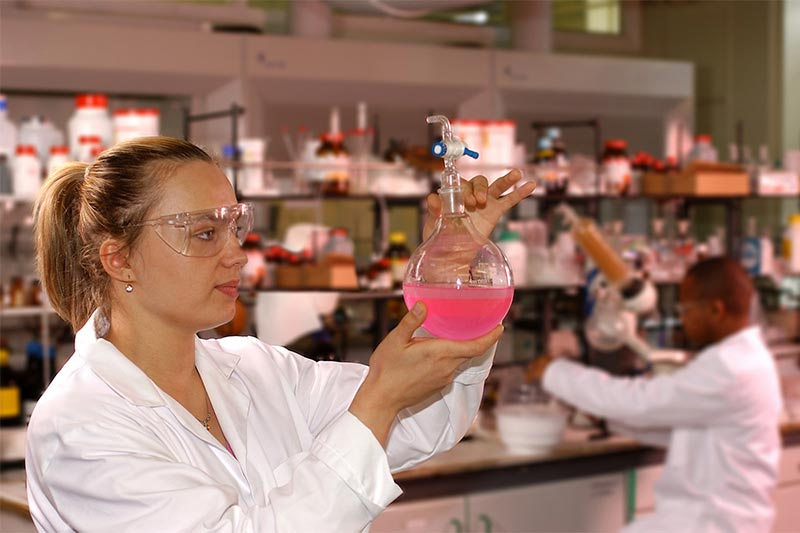 female student in lab coat examining a beaker filled with a pink liquid