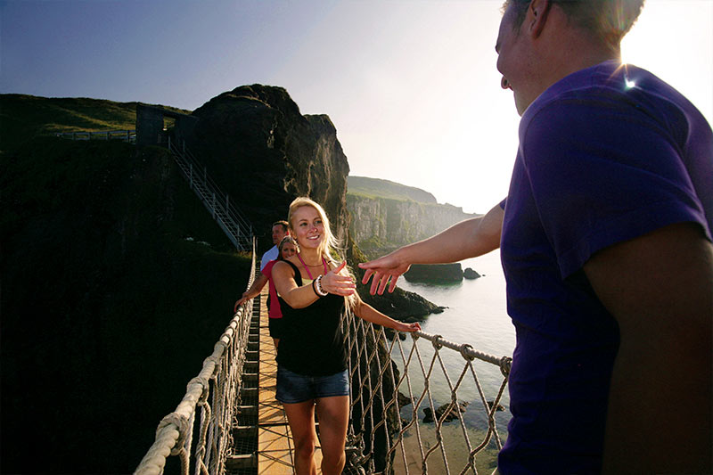 Students crossing carrick-a-rede rope bridge in the sunshine