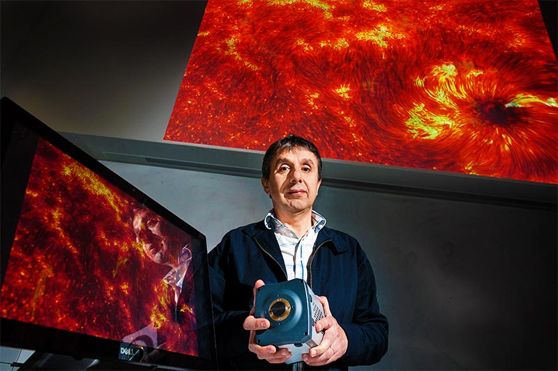 Lecturer with imaging device in front of a large galaxy display