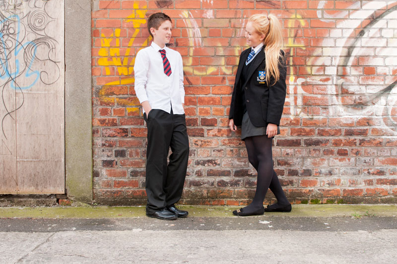two teenagers in different school uniforms in front of a graffittee sprayed brick wall