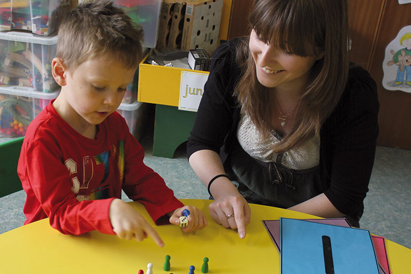 undergraduate student helping primary school pupil with counting