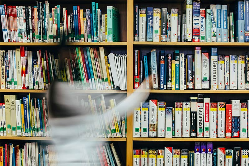 female student walking past the learning resources in the Queen's Language Centre library