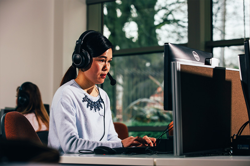 Female student wearing headphones and using a computer in the Queen's Language Centre