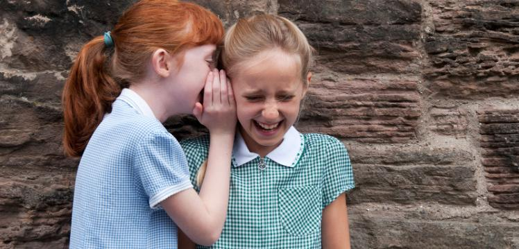 photograph of two primary school aged girls in different school uniforms whispering.