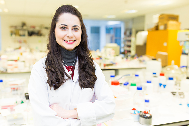 Image of a PhD student standing in a laboratory