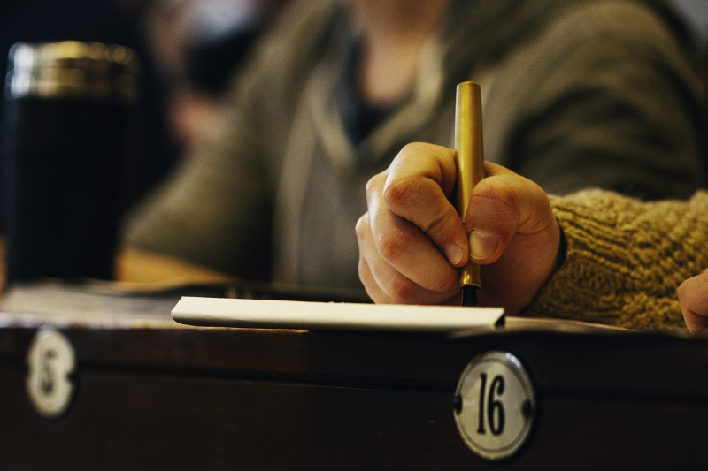 close up of student's hand holding a pen and taking notes