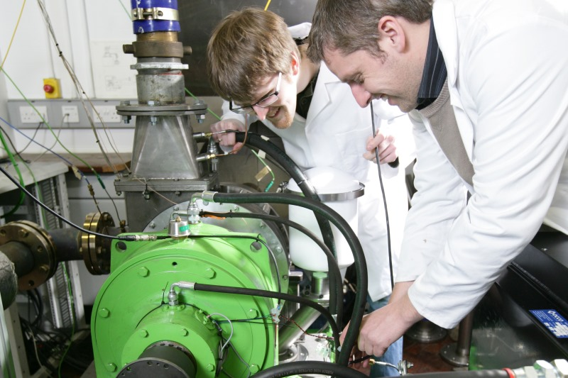 Researchers working with engine equipment