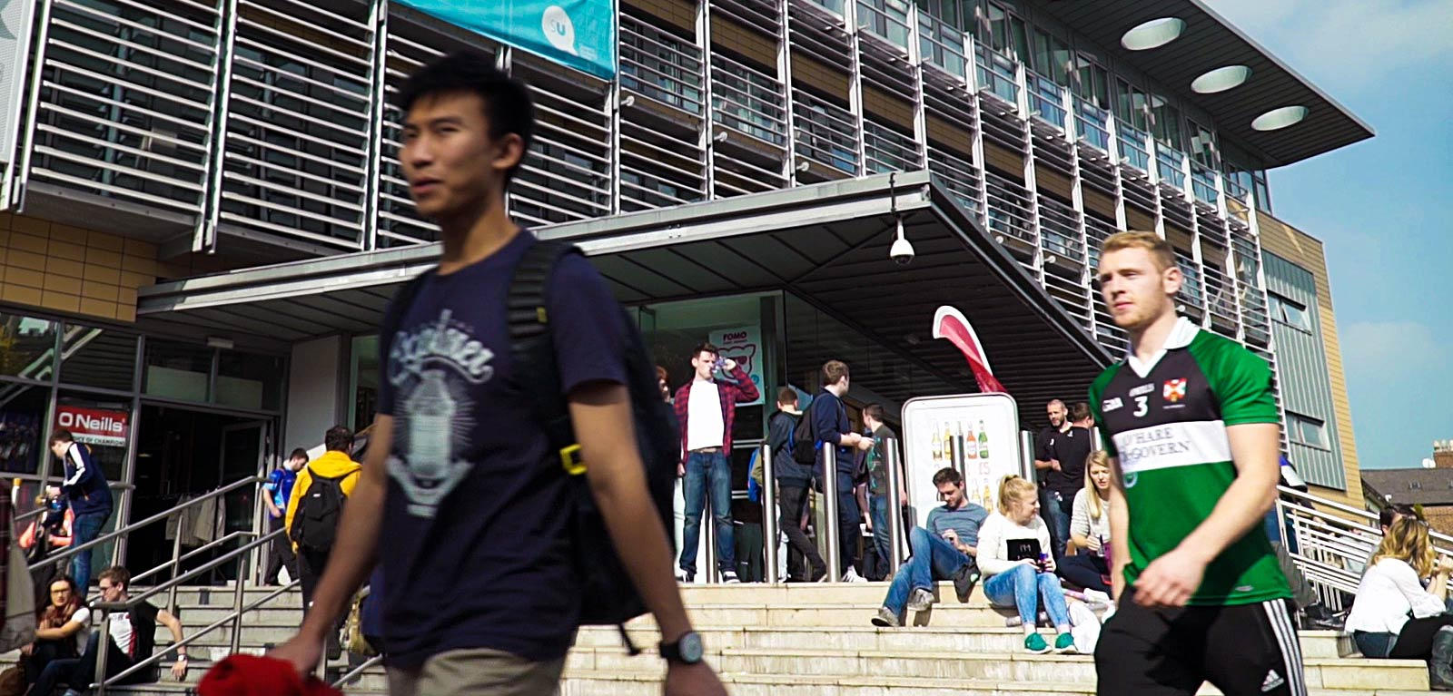 students walking past the exterior of the Queen's University Belfast Students' Union (QUBSU)