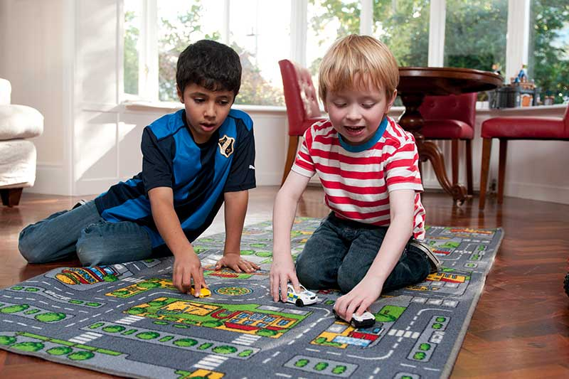 Two primary school aged boys playing with toy cars.