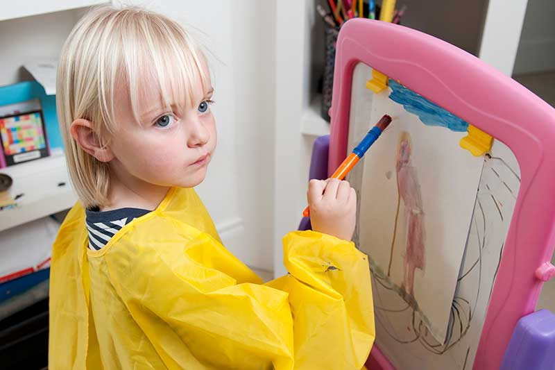 Pre-school aged girl painting at an easel in a school setting.