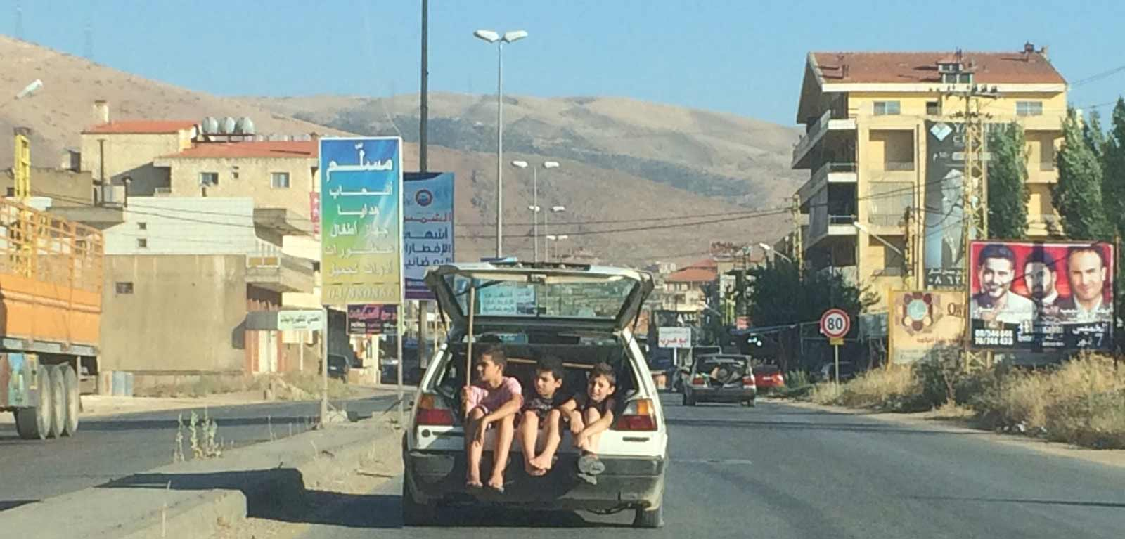 Three children sitting in the open boot of a car in a middle eastern town