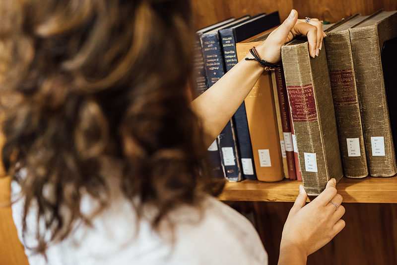Close up of a student lifting a book in the Special Collections room of The McClay Library