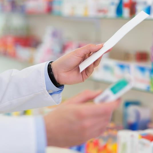 An image of a pharmacist holding a prescription.