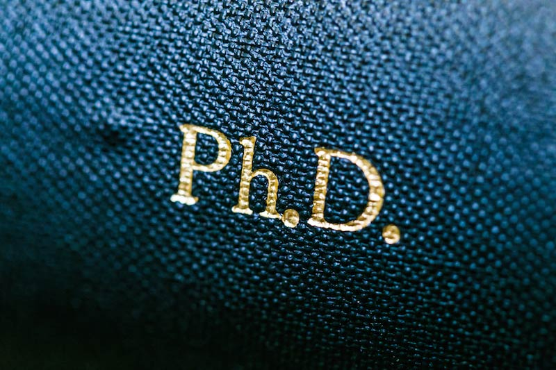 Close up of the letters PhD in gold on a blue book cover