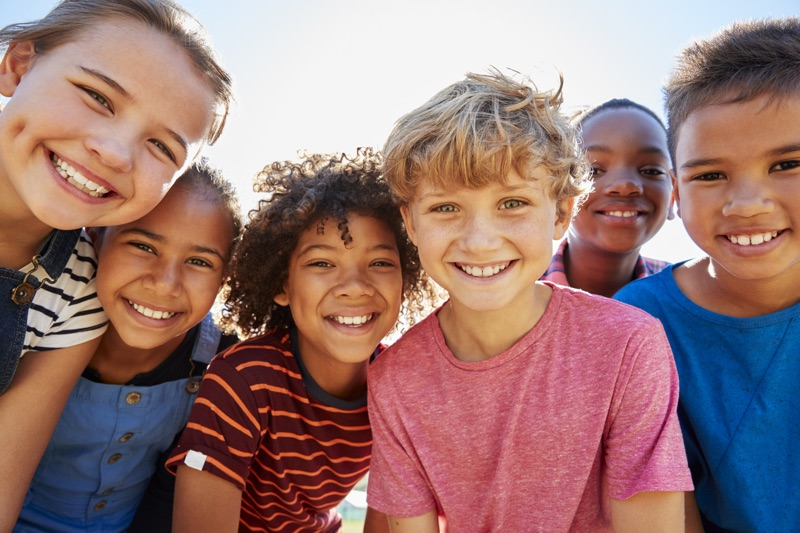 group photo of children smiling in the sunshine