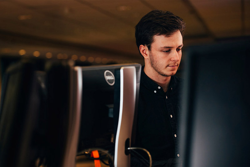 A man standing in front of a computer monitor
