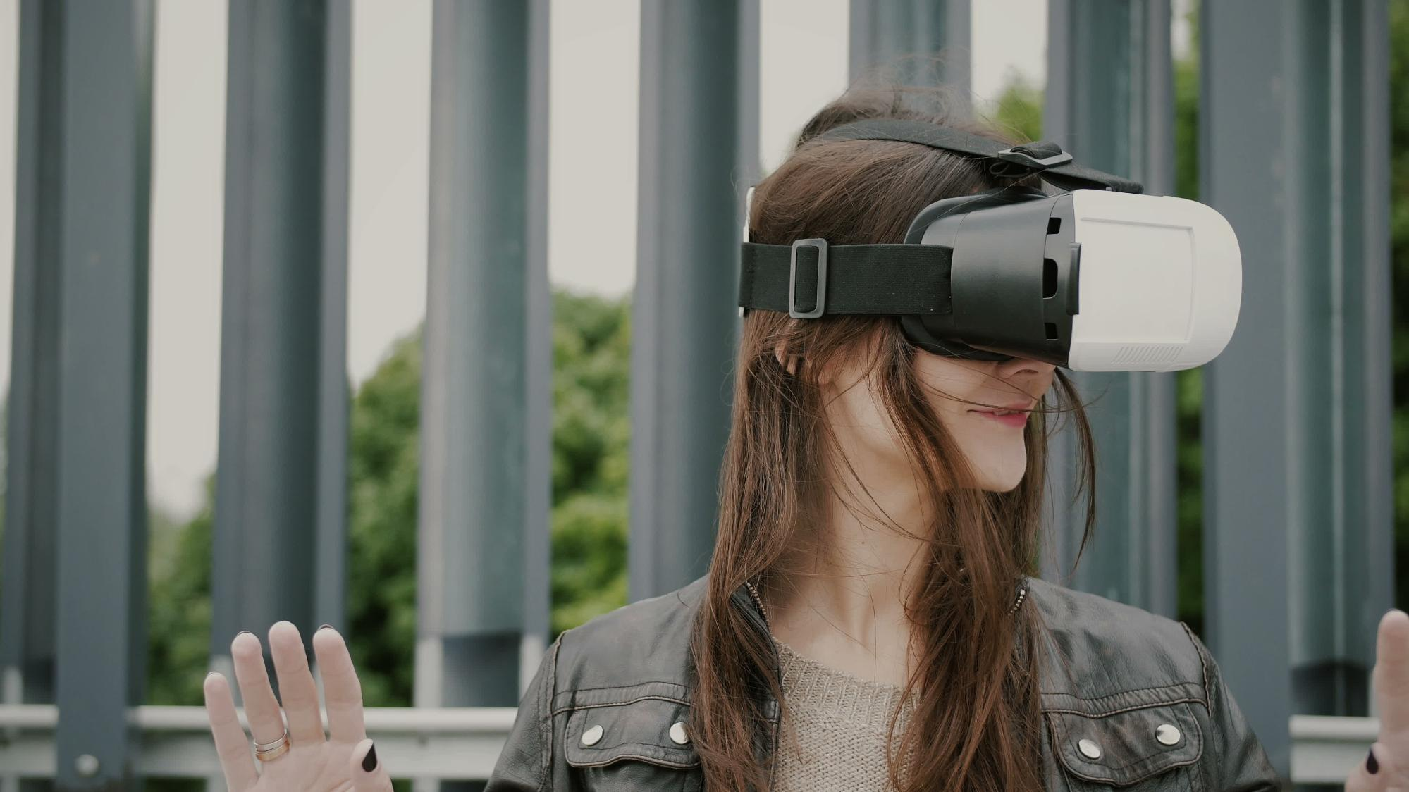 A woman wears a VR headset with a fence in the background