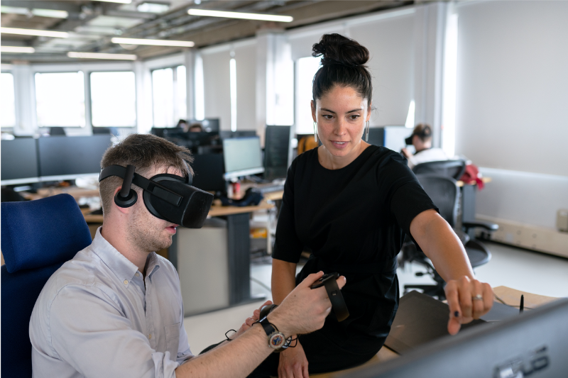 A man uses a VR headset and his colleague supervises