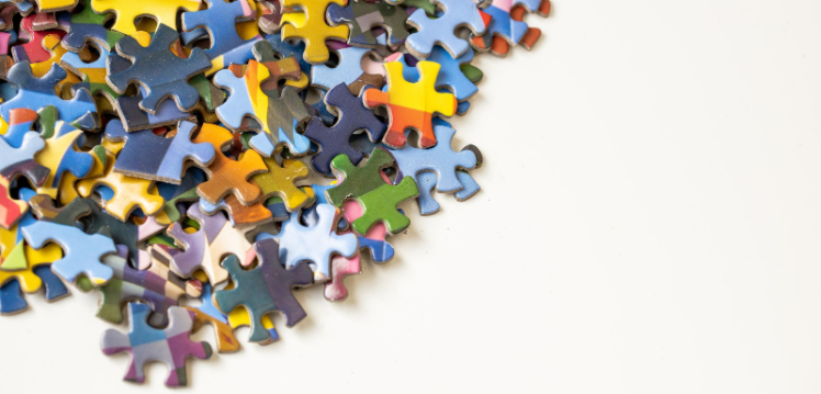 Photograph of multicoloured jigsaw puzzle pieces on white background
