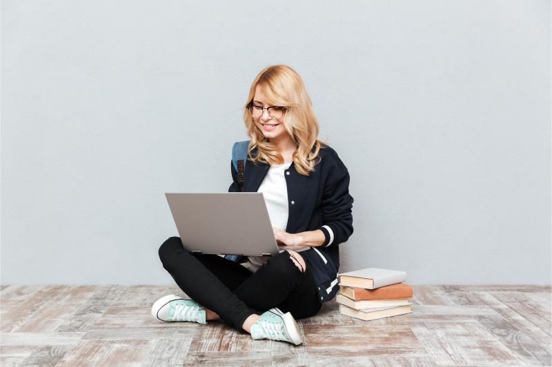 Girl sitting on floor with laptop and books