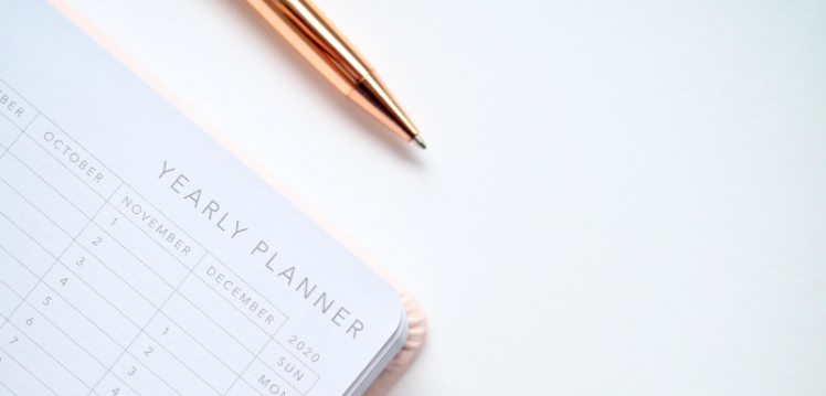 corner of an open calendar or yearly planner with a gold coloured biro pen sitting at the top