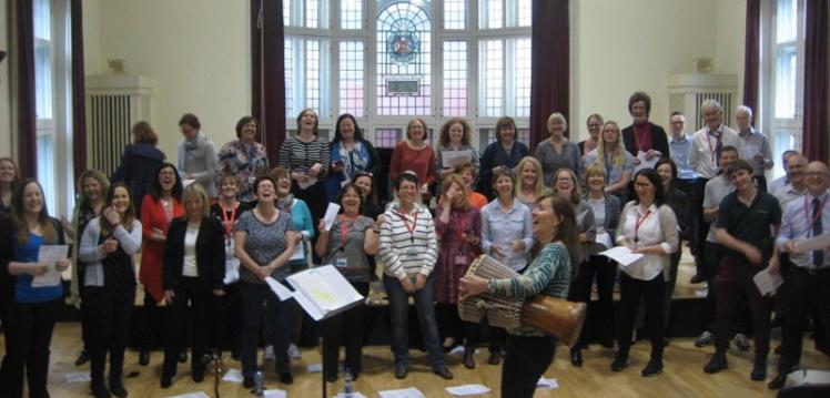 Queen's University Staff Wellbeing Choir practising and laughing in the Harty Room at Queen's